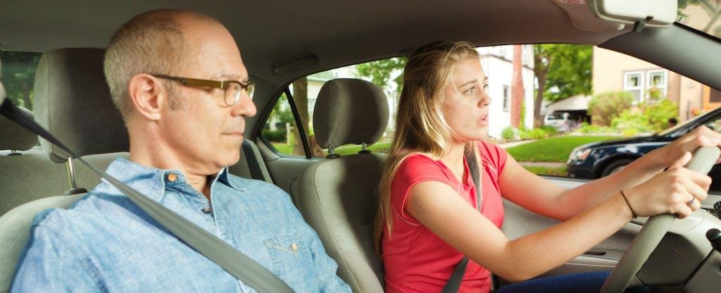Un père et sa fille adolescente conduisent une voiture ensemble