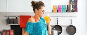 Une femme boit du jus dans sa cuisine