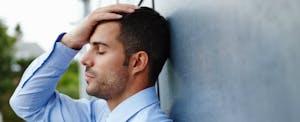 Un homme pose sa tête contre un mur. Il est stressé parce que ses comptes sont en cours de recouvrement.