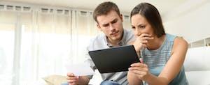 Un couple regarde une tablette et essaie de comprendre comment déposer un avis de contestation.