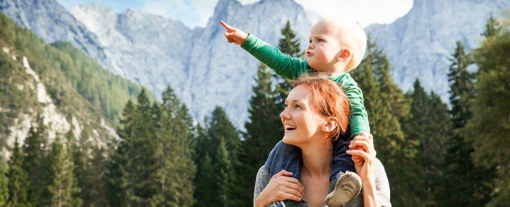 Une mère porte son bébé sur ses épaules alors qu'elles explorent les montagnes