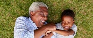 Un grand-père qui rit joue avec son petit-fils sur la pelouse