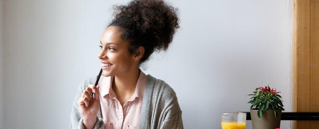 Une femme souriante regarde par la fenêtre avec un crayon appuyé sur sa bouche