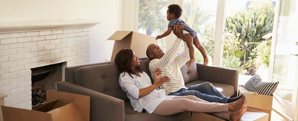 Les parents jouent avec leur bébé sur le canapé