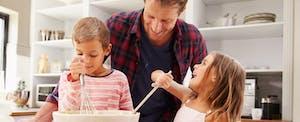Un père cuisine dans la cuisine avec ses enfants