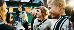 Young group of clubgoers drinking and catching up together while dancing at a trendy open air nightclub.