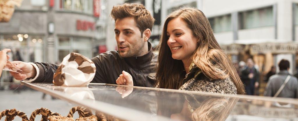 Un couple payant des pâtisseries au comptoir d'un boulanger