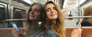 Portrait of smiling young woman and her mirror image in underground train. She wonders what a line of credit is.
