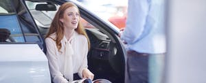 Car dealer talks to client as she reviews options at the dealership