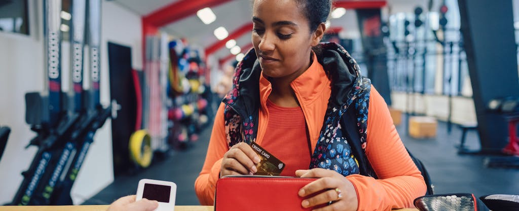 Woman in the gym deciding whether to pay for her new year's resolution with a with credit card