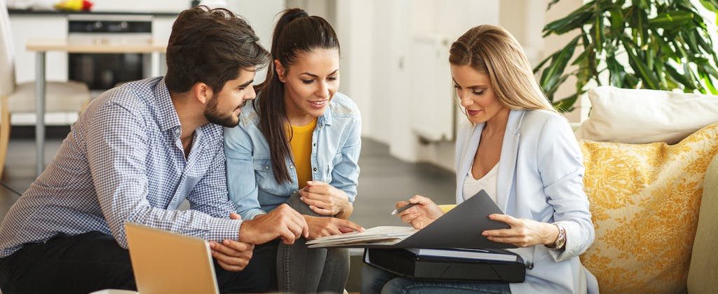 Female Real Estate agent offers insurance to young couple.