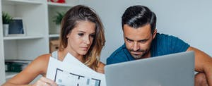 Young couple looking at blueprints and a computer to find the best rate for a mortgage