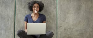 College student using laptop and blowing bubble gum bubble