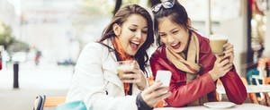 Two women sitting outside, looking at a cellphone together