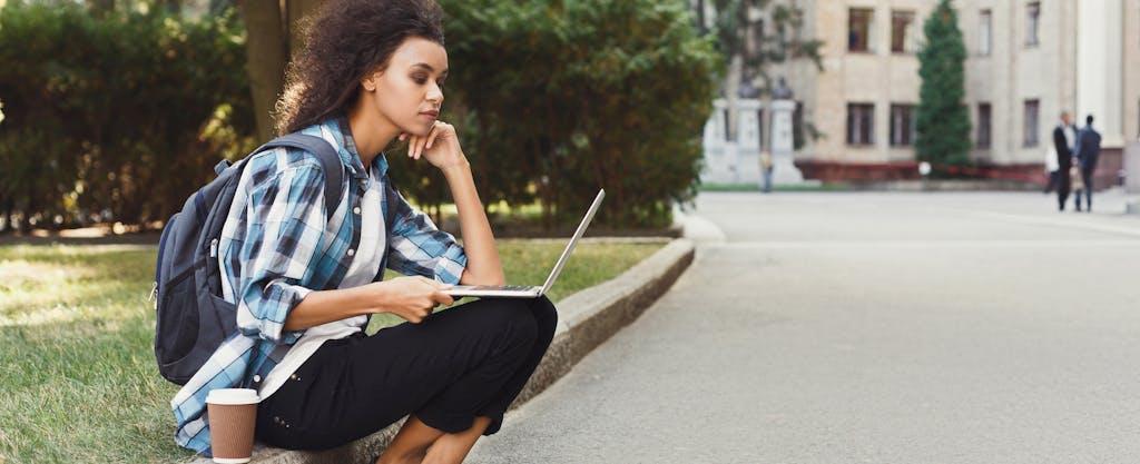 woman outside checks laptop