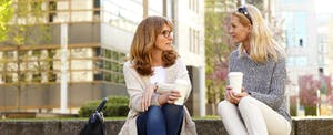 Two friends sitting outside, drinking coffee, and talking about how to pay your credit card bill