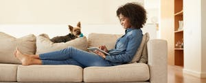 Young woman relaxing on sofa with her dog and looking at her digital tablet