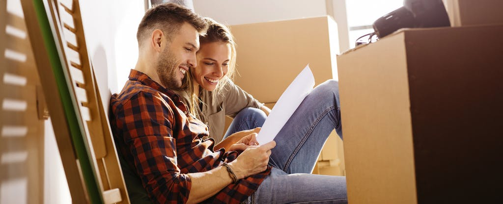 Couple reading a letter while sitting on the floor with moving boxes